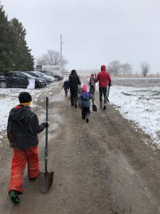 Adults and children with shovels walking